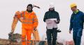 Maçons et chef d'équipe portant un casque de chantier et des EPI