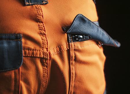 Gesäßtasche mit Reißverschluss und Knopf der Warnschutzhose in Orange title=