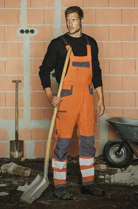 Handwerker im Warnschutz Outfit Orange mit NEON Latzhose