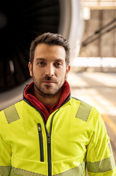 Handwerker trägt Warnschutz Softshelljacke in Gelb