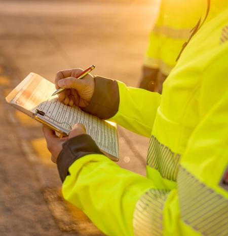 Handwerker macht sich Notizen in Warnschutz Softshelljacke Gelb